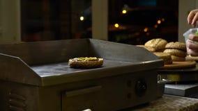 Вождь брызгает с мустардом плюшку для бургера и кладет замаринованные огурцы Кашевар варит сток-видео