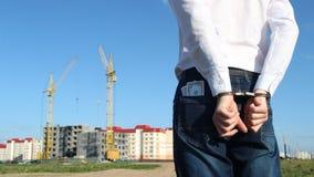 Вождь в белой рубашке с долларами денег надеван наручники против фона строить дом акции видеоматериалы
