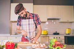 Вождь в pron стоит на таблице в грибах кухни и отрезка с ножом Он смотрит эти процесс и улыбки Гай стоковое фото