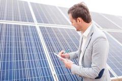Вождь делает примечания в тетради смотря солнечную батарею стоковое изображение rf