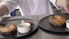 Вождь кладет 2 черных блюда с стейками рыб к стальной таблице на кухню в ресторан акции видеоматериалы