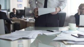 Вождь смотря планы для офиса в месяц и подготавливая задачи для сотрудников сток-видео