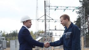 Вождь трясет руки с работником на фоне электростанции видеоматериал