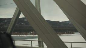 Вождение автомобиля на мосте над широким рекой Взгляд ландшафта с горами решетка утюга строба загородки большого кирпича декорати видеоматериал