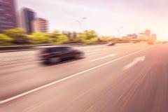 Вождение автомобиля на дороге на заходе солнца, нерезкости движения Стоковое Изображение
