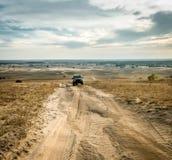 Вождение автомобиля на свернутой дороге в поле Стоковое Изображение RF