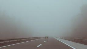 Вождение автомобиля на тумане шоссе входя в Стоковое Изображение RF