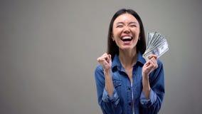 Возбужденная азиатская женщина с банкнотами доллара, победитель лотереи, удача, везение стоковые фото