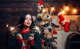Возбужденная женщина в красном настоящем моменте удерживания обмундирования Санта Клауса Канун Нового Года женщины Привлекательна стоковые изображения rf