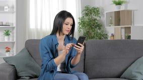 Возбужденная женщина празднуя хорошие новости проверяя телефон акции видеоматериалы