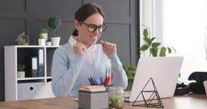 Возбужденная коммерсантка получая хорошие новости пока работающ на ноутбуке акции видеоматериалы