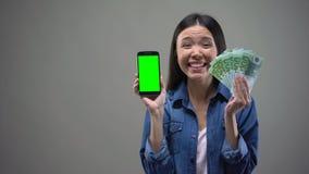 Возбужденная молодая дама держа банкноты смартфона и евро, онлайн победителя лотереи видеоматериал