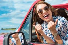 возбужденная молодая женщина в солнечных очках сидя в автомобиле и показывая большие пальцы руки вверх стоковое изображение rf