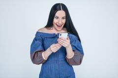 Возбужденная молодая женщина изумленная невероятным ходя по магазинам мобильным сообщением продажи приложения смотря смартфон, эй стоковая фотография rf