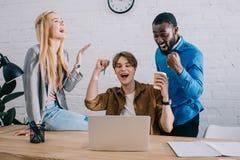 возбужденные многокультурные предприниматели празднуя на таблице с ноутбуком в современном стоковые изображения
