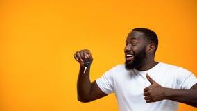 Возбужденный Афро-американский ключ автомобиля удерживания человека и показывать большие пальцы руки вверх, приобретение стоковые фотографии rf
