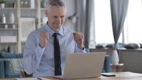 Возбужденный бизнесмен волос серого цвета празднуя успех, работая на ноутбуке