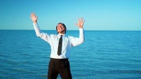 Возбужденный бизнесмен кричащий и поднимая руки к небу морем, замедленным движением акции видеоматериалы