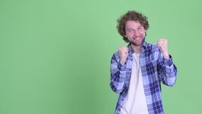 Возбужденный молодой бородатый человек хипстера указывая на сторону видеоматериал