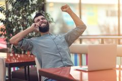 Возбужденный счастливый бородатый фрилансер читая электронную почту с результатами о победе в современном онлайн состязании сидя  стоковое фото