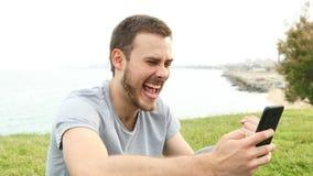 Возбужденный человек проверяя телефонные сообщения видеоматериал