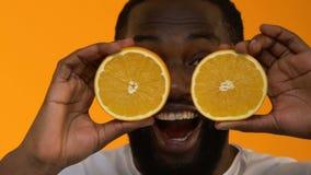 Возбужденный чернокожий человек держа свежие оранжевые половины, сотрясенные энергичным питанием? видеоматериал