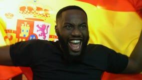 Возбужденный черный вентилятор развевая испанский флаг, радуясь национальная победа спортивной команды акции видеоматериалы