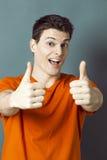 Возбуженные атлетические человек 20s и большие пальцы руки вверх для о'кей или успеха Стоковые Изображения
