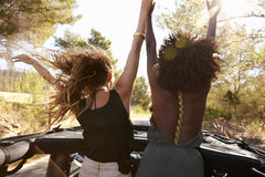 2 возбужденных женщины стоят позади открытого автомобиля, заднего взгляда Стоковое Фото