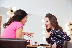 2 возбужденных, который интересуют молодой женщины говоря в салоне красоты Стоковое Изображение