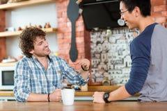 2 возбудили жизнерадостных парней сидя, говоря и смеясь над в кафе Стоковая Фотография RF