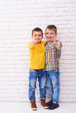 2 возбудили мальчиков обнимая один другого и показывая большие пальцы руки вверх Стоковое Изображение