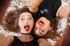 2 возбудили милых женщин принимая selfie и лежать Стоковые Фотографии RF