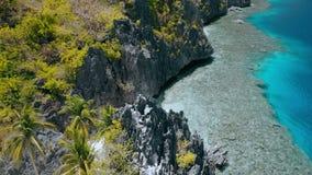 Воздушная муха над святыней Matinloc вдоль береговой линии El Nido, Palawan, Филиппины Эксцентричные утесы горы известняка и акции видеоматериалы