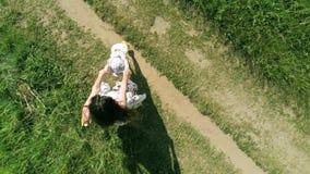Воздушная надземная съемка мамы и ее меньшей детской игры совместно и закрутки вокруг удержания рук акции видеоматериалы