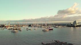 Воздушная съемка Марина, гавань в небольшом удя городке на береге Тихого океана Большое количество шлюпок, яхты акции видеоматериалы