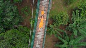 Воздушная съемка молодой женщины и ее маленького сына кладя на висячий мост над джунглями Перемещение к юговосток видеоматериал