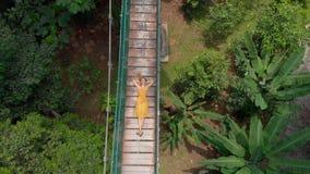 Воздушная съемка молодой женщины кладет на висячий мост над джунглями Перемещение к концепции Юго-Восточной Азии акции видеоматериалы