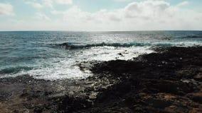 Воздушная съемка над волнами моря ударяя скалистый пляж брызгая против утесов Голубое небо с дорогой солнца на горизонте Океан на сток-видео