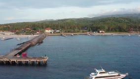 Воздушная съемка небольшого города с портом на тропическом острове, захода солнца со шлюпками и океана на маленьком городе на вос акции видеоматериалы