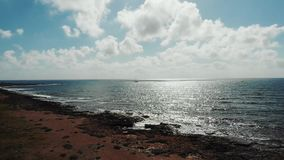 Воздушная съемка отражения солнечного света на волнистом море во время захода солнца Волны ударяя против скалистого пляжа Морское видеоматериал