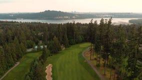 Воздушная съемка смотря вниз с прохода поля для гольфа устроенного удобно в лесе с целью входа Burrard на заднем плане на акции видеоматериалы