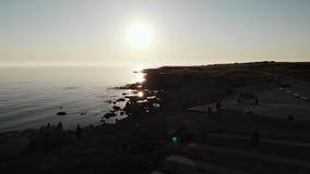 Воздушная съемка темных силуэтов пешеходов и велосипедиста отдыхая около пляжа города с солнцем и скалистого пляжа в предпосылке  сток-видео