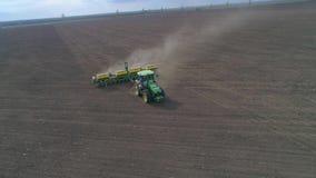 Воздушная съемка фермера в современном тракторе работает на сухом поле во время вспахивать на весеннем сезоне сток-видео