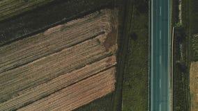Воздушное движение над большущим вспаханным черным полем и зеленым лугом отделенными бесконечной дорогой асфальта
