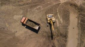 Воздушное фото экскаватора льет песок в тележку На взгляд сверху строительной площадки стоковая фотография