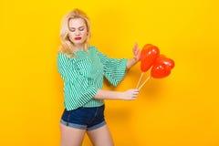 Воздушные шары белокурым владением женщины в форме сердц Стоковое Фото