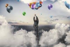 Воздушные шары бизнесмена reacing стоковая фотография rf