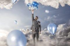 Воздушные шары бизнесмена reacing стоковые фото