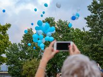 Воздушные шары гелия летают в небо и женщина фотографирует ее с мобильным телефоном стоковая фотография rf